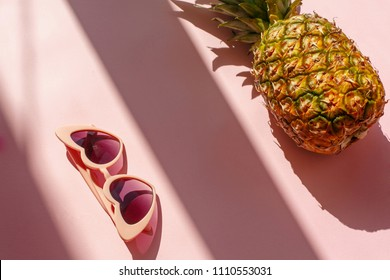 juicy pineapple and pink sunglasses on trendy pink paper background in sun light. flat lay. creative contrast summer image. vacation and party concept. space for text. tropical summer holidays