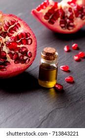 Juicy pomegranates on black stone. Pomegranates oil