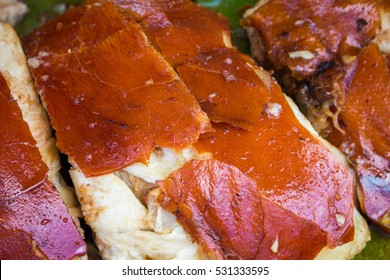 Juicy pork meat cooked on grill. Sliced pork barbecue with gold skin. Spanish dish lechon close image for restaurant menu or eatery illustration. Tasty meat ready for eat. Traditional cuisine of Spain