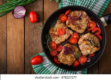 Juicy pork steak with rosemary and tomatoes on pan. Top view