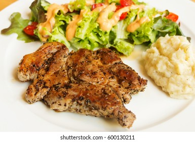 juicy pork steak with salad and mash potato on white plate
