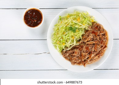 juicy pulled meat tossed in sauce on plate with fresh spring coleslaw corn salad served on wooden cutting board with fork, homemade barbecue sauce and slice of lime, view from above