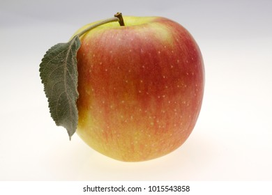 juicy red apple over on white with leaf
