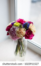Juicy and rich spring bouquet of pink peonies, Green and Blueberry roses, peach carnations, callas, purple eustomas and violet hyacinths on the window background. Brightful fresh mixed flowers in vase