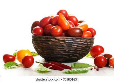 Juicy ripe colorful cherry tomatoes in a clay bowl against a light background. Place for text (top). Organic food, harvest