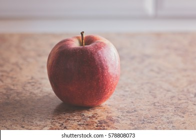 a Juicy ripe red apple  on the table brown marble