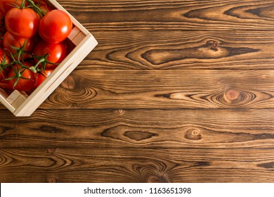 Juicy ripe red organic tomatoes in a wooden crate placed in the corner on a rustic wooden table at farmers market with copy space viewed from above
