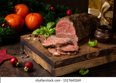 Juicy roast beef with spices sliced on a cutting Board, delicious meat, traditional food. Christmas holidays, new year, menu on dark background