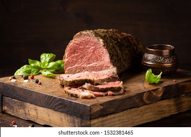 Juicy roast beef with spices sliced on cutting Board, delicious meat, traditional food. On dark background
