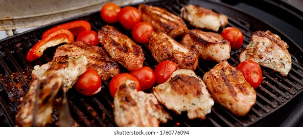 juicy roasted meat, tomatoes, red pepper on the grill on the street