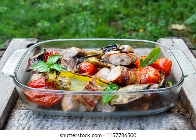 Juicy sausages and grilled vegetables in a glass bowl on a nature background. Dinner outdoors. Garden party.