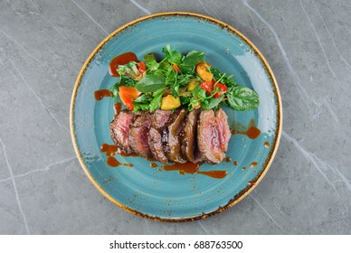 Juicy Skirt steak in addition with a vegetable garnish. Dish from the chef