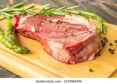 Juicy slice of fresh pork on wooden deck decorated with blach pepper, rosemary and aspargus
