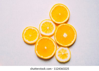 Juicy slices of an orange on a white, fruity background, top view.