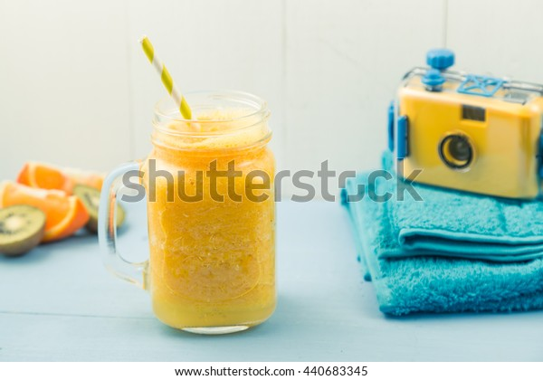 Juicy smoothie from orange, mango or pineapple, beachfront set with blue towels and camera, healthy life concept, summer vacation