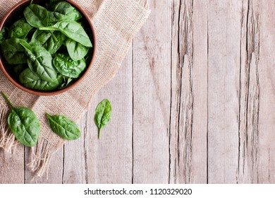 Juicy Spinach Leaves in a Bowl on a rustic Wooden Table. Top view. Healthy  Food- Image