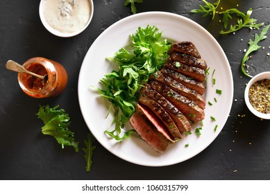 Juicy steak medium rare beef with green salad on white plate over black stone table. Top view, flat lay