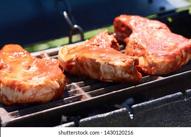 Juicy steak on the bone on the grill. Grilled beef or pork