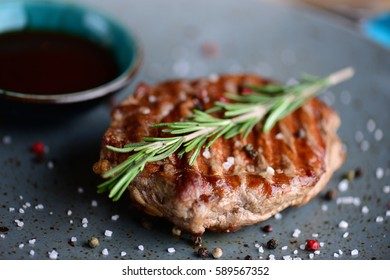 Juicy steak on an plate with sauce serving for a dinner in a steakhouse. Macro food background. Close up...