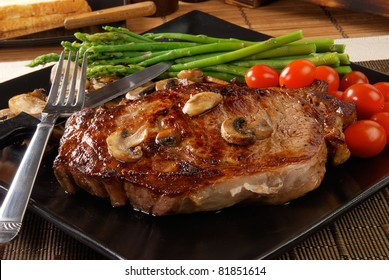 A juicy steak with sauteed mushrooms, cherry tomatoes and asparagus