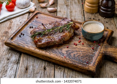 juicy Striploin Steak on the board with rosemary and pepper sause