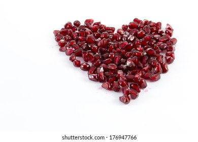 Juicy sweet delicious pomegranate seeds heart isolated on white background
