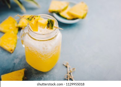 Juicy sweet summer drink cocktail with pineapple and ice in jar on blue table.