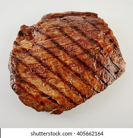 Juicy thick medallion of lean flank beef steak marinated and grilled over a summer BBQ viewed close up from above over white
