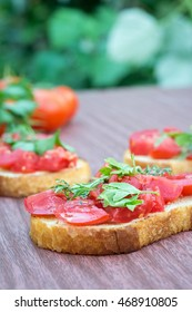 Juicy tomatoes on toasted bread with herbs. Marsala wooden table. Selective focus