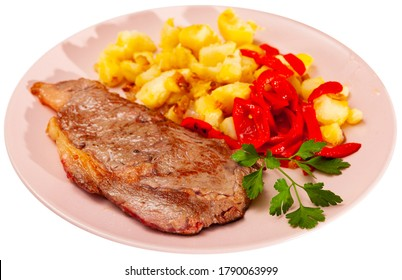 Juicy veal steak with vegetable garnish of fried potatoes, pickled bell pepper and fresh greens. Isolated over white background