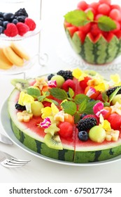 Juicy watermelon pizza with summer fruits and edible flower.Selective focus.