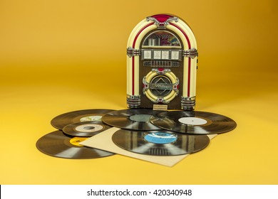 Jukebox and some old vinil records, isolated in yellow background