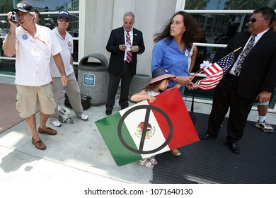 Jul 13, 2008 - San Diego, California, USA - A wife and daughter of a Minuteman rush away holding an anti-Mexico sign after arguing with a pro-immigrant man outside of the San Diego convention center.