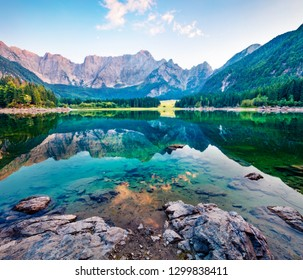 Julian Alps in the morning mist. Amazing summer view of Fusine lake. Majestic outdoor scene with Mangart peak on background, Province of Udine, Italy, Europe. Traveling concept background.