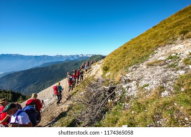 JULIAN ALPS, SLOVENIA, 10. SEPTEMBER 2011: A large group of female hikers on a mountain path hiking towards Vodnik mountain hut in Julian Alps on a sunny day.