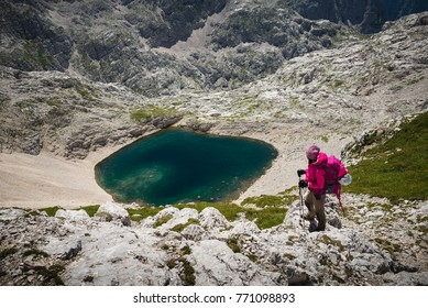 Julian Alps, Slovenia -  7 29 2017 :  Young famale is admiring Krisko lake in Julian Alps, Slovenia.