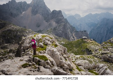 Julian Alps, Slovenia - 7 29 2017 : Young female is trekking in the Julian Alps, Slovenia. Kriski podi and the Pogacnik hut can be seen in the distance.