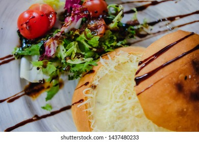 Julienne in a bun with healthy salad decorated balsamic sauce. Edible plate made of bread