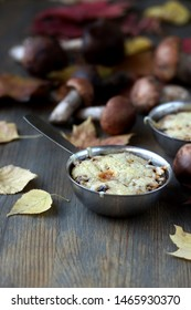 Julienne with forest mushrooms. Mushrooms are baked in cream and with cheese. Autumn leaves.