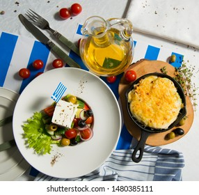 Julienne and greek salad on the table with flag of greece top view. Lunch at the restaurant.