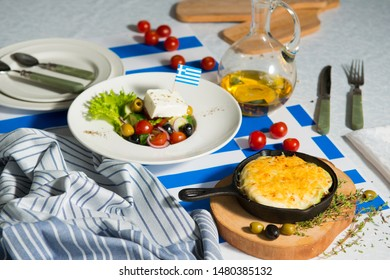 Julienne and greek salad on the table with flag of greece. Lunch at the restaurant.