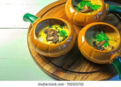 Julienne with mushrooms champignons cheese and parsley in a pot / Julienne in a pot