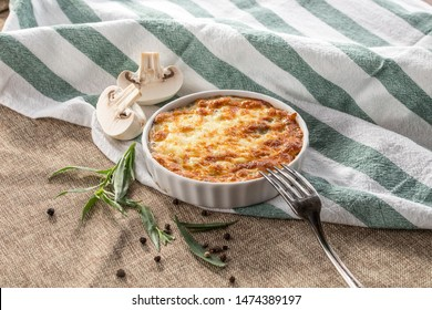 julienne with mushrooms and melted cheese on grey tablecloth side view
