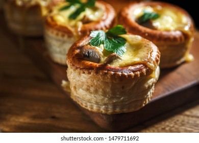 Julienne with mushrooms in puff pastry tartlets seasoned with herbs on a wooden stand close-up