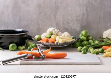 Julienne Peeler served with fresh greens ready to cook: Brussels cabbage, asparagus, baby corn, cauliflower and bamia with metal steamer over a white background.