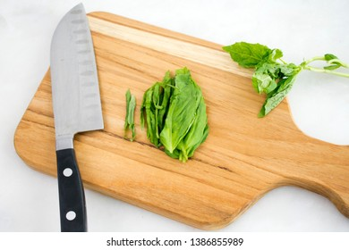 Julienned Basil Leaves on a Cutting Board