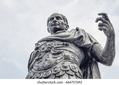Julius Caesar wearing armor makes an assertive gesture while seemingly he addresses his soldiers