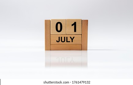 july 1 1st first. Day 1 of month, handmade wood cube calendar on white glossy background with reflection. summer month, day of the year concept.