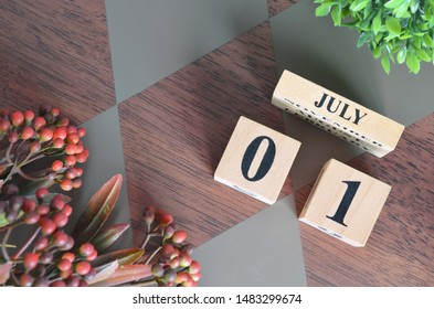 July 1. Date of July month. Number Cube with a flower leaves and bush on Diamond wood table for the background