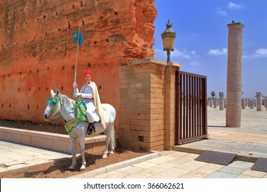 July 10, 2015: Traditional guard on a white horse near the ruins of an old mosque and Hassan Tower in Rabat, Morocco